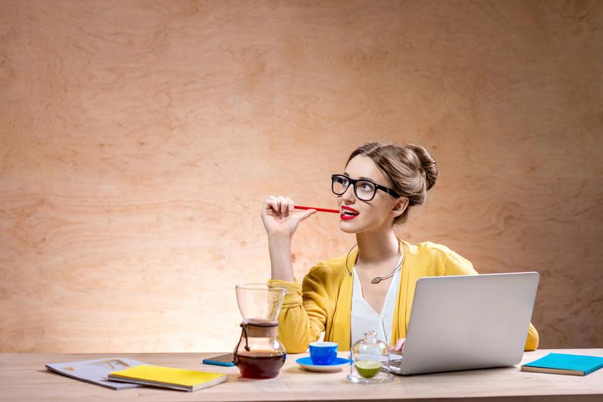siedząca w kawiarni młoda kobieta pracuje nad czymś korzystając z notatnika i tabletu
