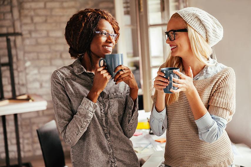 Dwie dziewczyny stoją pijąc gorącą herbatę
